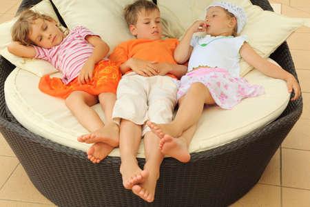 cansancio: dos chicas y un chico poco cansado acostado en silla círculo grande con almohadas y con resto