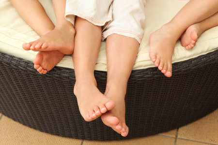 calabria: legs of three barefooted children lying on circle sofa