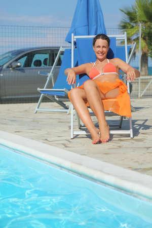 mandatariccio: young woman in orange bikini and pareo sitting on beach chair near pool and smiling