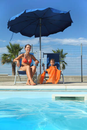pareo: young mother in orange bikini and daughter sitting on beach chair near pool and smiling, palms