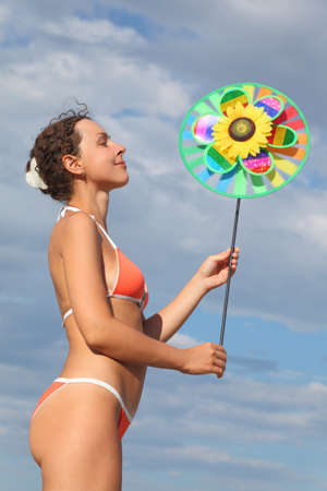 young beauty woman in orange bikini standing and holding pinwheel toy, looking on it and smiling photo