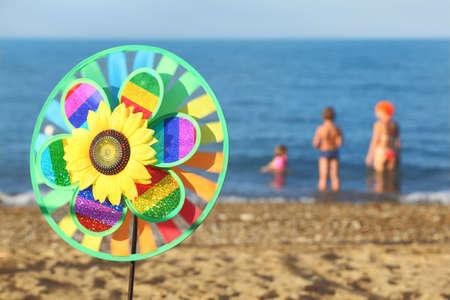 veelkleurige pinwheel speelgoed met bloem op het strand, familie staande in het water Stockfoto
