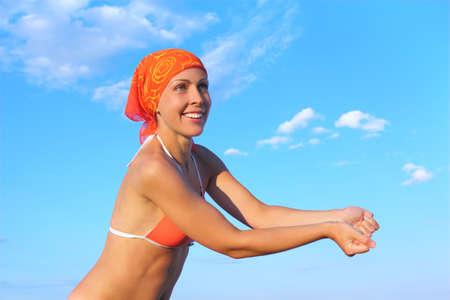 beauty woman in orange bikini and bandana playing volleyball, beat pose, blue sky photo