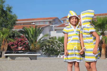 mandatariccio: two little girls standing on beach and holding for hands, closed eyes, palms and building