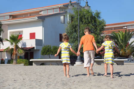 mandatariccio: little boy and two girls walking on beach, holding for hands, view from back, trees and building