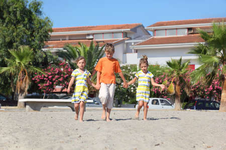 little boy and two girls walking on beach, holding for hands, front view, palms and building photo
