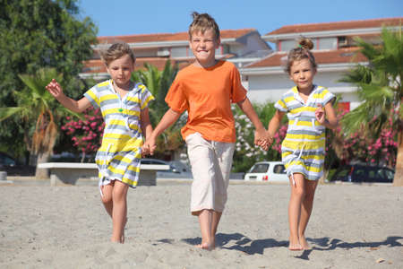 three palm trees: little boy and two girls walking on beach, holding for hands, palms and building Stock Photo