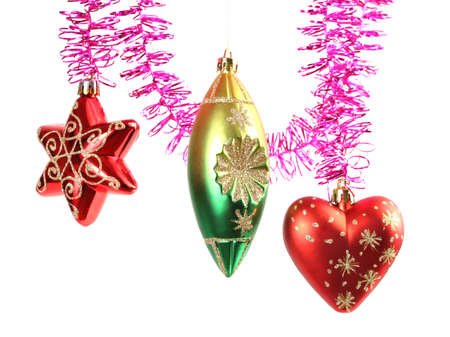 Various colorful christmas-tree decorations hanging on purple tinsel photo