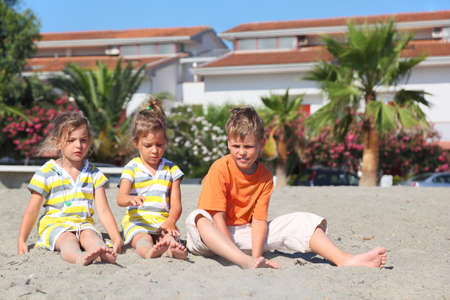 three palm trees: little boy and two girls sitting on beach, palms and building