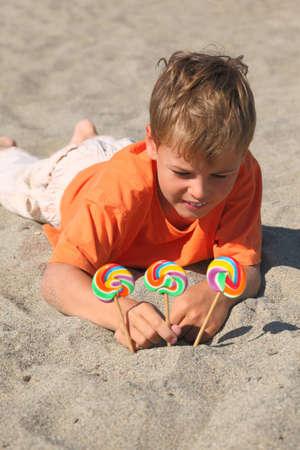 mandatariccio: caucasian boy in orange shirt lying on beach, multicolored lollipops stick into sand