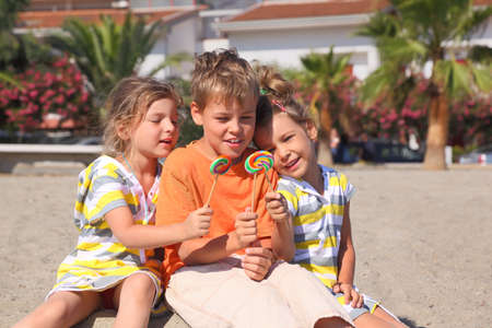 little boy and two girls sitting on beach and holding multicolored lollipops, palms and building Stock Photo - 12627329