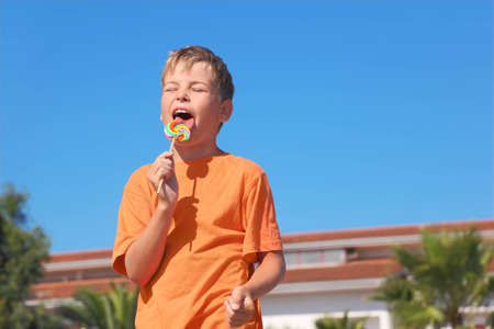 little boy in orange shirt licking multicolored lollipop, closed eyes, palms and building Stock Photo - 12621471