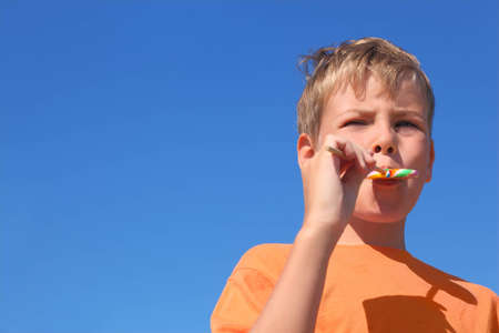 little boy in orange shirt eating multicolored lollipop, blue sky Stock Photo - 12620144