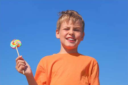 little boy in orange shirt holding multicolored lollipop, blue sky Stock Photo - 12623178