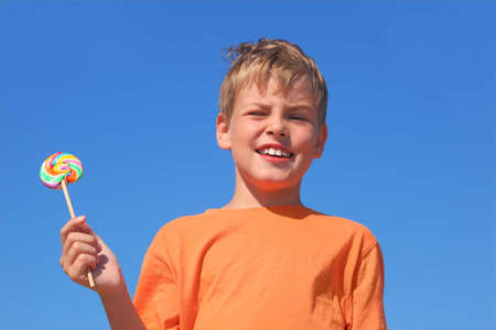mandatariccio: little boy in orange shirt holding multicolored lollipop, blue sky