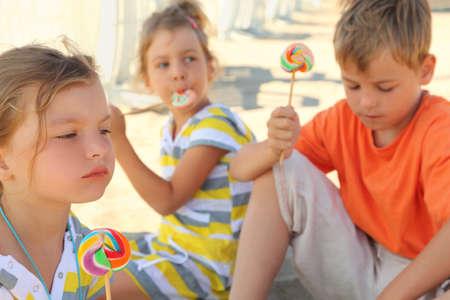 bambini seduti: bambini gravi seduti sulla spiaggia e mangiare lecca-lecca, concentrarsi sulla ragazza di fronte
