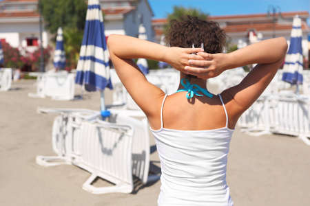 mandatariccio: womans back in white shirt, hands over head, lounges, umbrellas and houses Editorial