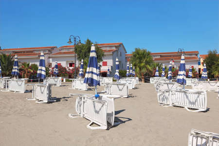 lounges: many lounges and umbrellas on beach near palms and houses, sunny day