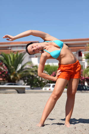 mandatariccio: young beauty woman making gym exercises on beach and smiling, house and palms