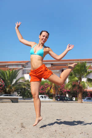 mandatariccio: young beauty woman jumping on beach and smiling, house and palms