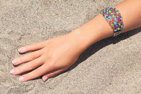 bangle: closeup of womans hand with multicolored bracelet on sand, sunny day Stock Photo