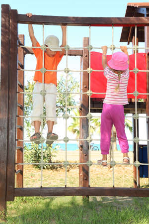 little boy and girl climbing on rope ladder at playground, sunny day, sea