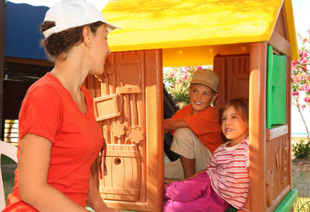mandatariccio: little boy and girl sitting in toy house at playground and looking on mother, sunny day