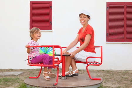 mandatariccio: mother and daughter sitting on merry-go-round at playground and smiling, white building