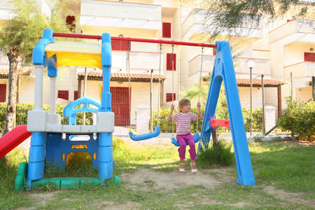 mandatariccio: little girl sitting on swing at playground and looking at side, sunny day, building Editorial