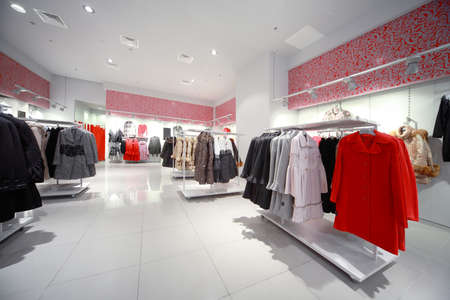 Inside the shop, gray-red hall with hanging outerwear - coats and jackets