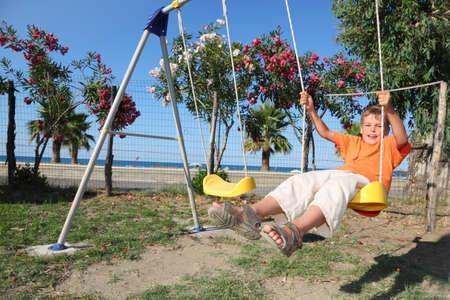 sandalias: niña sentada en el columpio en el patio de recreo, día soleado, los árboles con flores y el mar