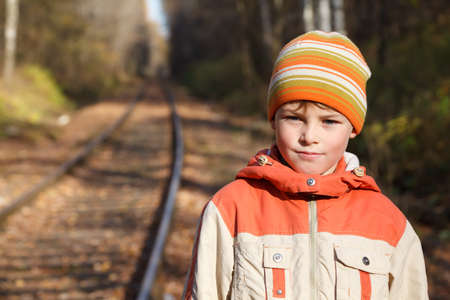 Portrait of boy autumn sunny day on railway. He is dressed in jacket and cap. photo