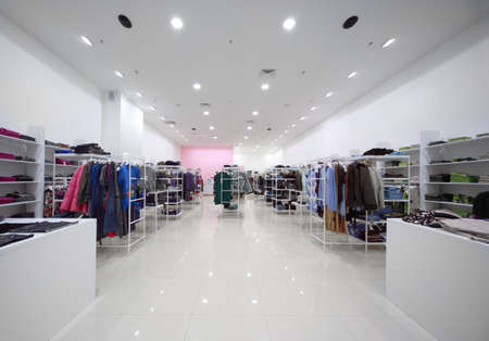 Inside the big shop, white hall with clothes on shelves and hanging outerwear