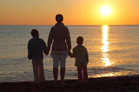 Moeder met twee kinderen, het aanbreken van de handen te staan op het strand persoon tot de zee en kijken bij zonsondergang