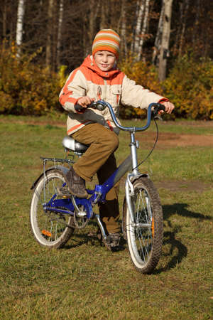 Boy on bicycle in autumn park on sunny day. He was wearing jacket and hat. photo