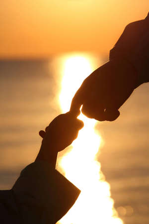ashore: Silhouettes of childs and grown man hands which adjoin fingers in  evening ashore exterminating during sunset