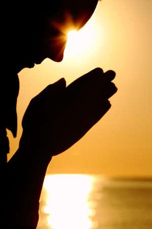 mano de dios: Silueta de mujer que se encuentra cerca del mar frente a Sol y dejó las manos antes de sí mismo y reza Foto de archivo