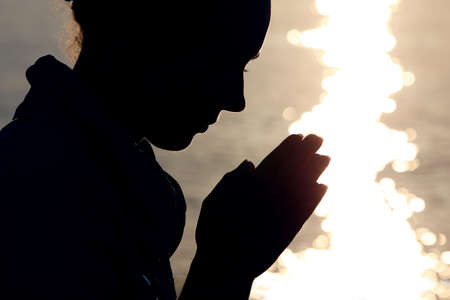 ashore: Silhouette of woman in  type, which sits ashore  and prays fold arms Stock Photo