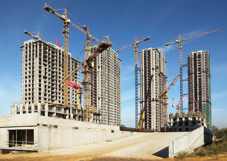 building site: Four tall buildings under construction with cranes against a blue sky