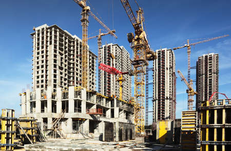 concrete commercial block: Inside place for many tall buildings under construction and cranes under a blue sky