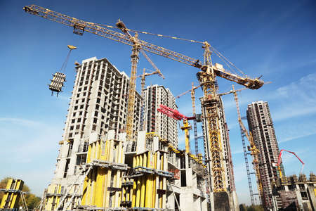 building site: Working on place with many tall buildings under construction and cranes under a blue sky