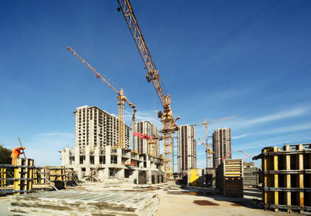 Working tall cranes inside place for with tall buildings under construction under a blue sky