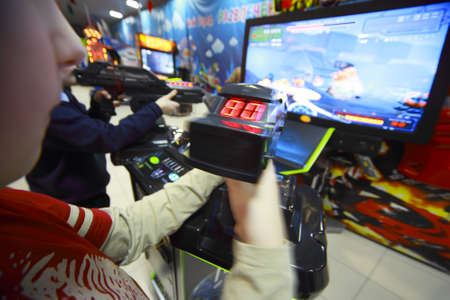 game show: Hands of boys playing video games, they hold joystick in front of the monitor Editorial