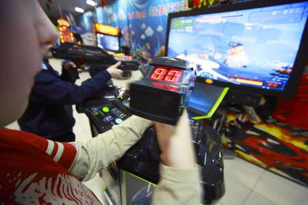jugando videojuegos: Las manos de unos niños que juegan juegos de video, que poseen joystick en frente del monitor Editorial