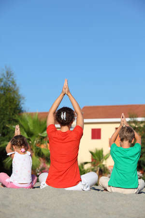 Woman with two children sit turn  back on sand in  pose of yoga and laying down hands lift hands upwards photo