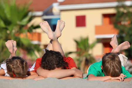 Two children with   mother sleep on  beach on  stomach, heaved up feet upwards and crossed them, focus on legs photo