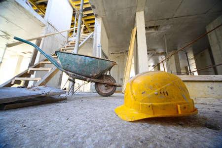 cantieri edili: Elmetti gialli e carrello piccolo a pavimento di cemento all'interno dell'edificio incompiuto