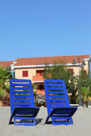 mandatoriccio: Two blue plastic chairs stand under  sun on  beach near cottages Stock Photo