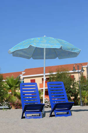 In  day-time on sand two dark blue plastic chairs cost under  beach opened blue umbrella photo