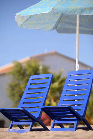 Two dark blue empty chairs stand  under  beach umbrella, focus on left chair photo